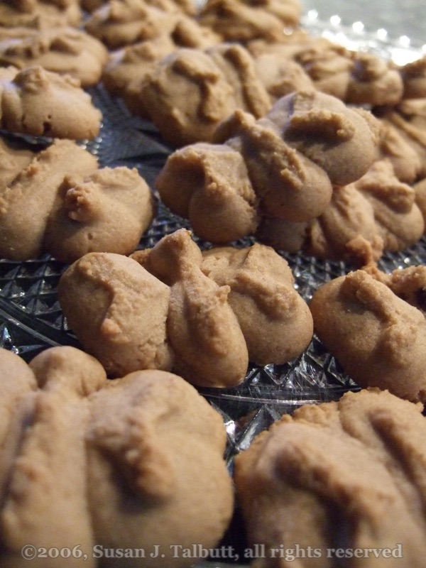 A plate of light brown, butterfly-shaped spritz cookies.