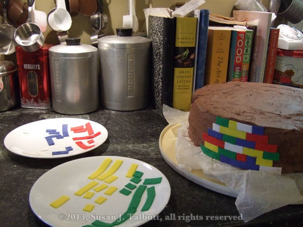 [Lego cake: 'bricks' made of fondant laid out to attach to cake, with cake partly covered in bricks, copyright 2013, Susan J. Talbutt, all rights reserved]