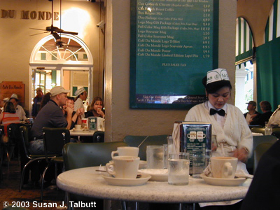 [A waitress counts her change at Cafe du Monde, December 2003]