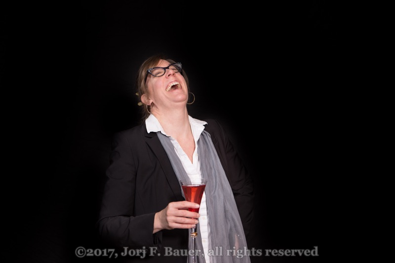 [Woman in a black jacket laughing with a champagne cocktail; copyright 2017 Jorj F. Bauer, all rights reserved]